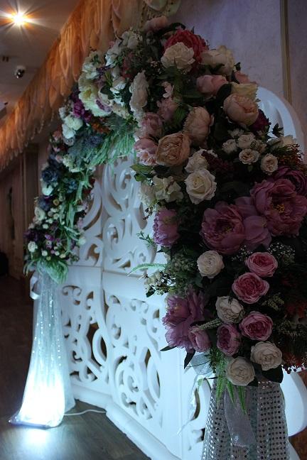 Арка декорированная цветами и материалом с подсветкой.